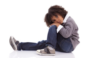 Portrait of an african american little boy sitting on the floor, isolated on white background